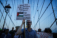 New York City, NY. 20 August 2014. A man holds a banner as he takes part during a Pro-palestine Rally across de Brooklyn Bridge in Manhattan.  Photo by Kena Betancur/VIEWpress