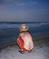 "Man with a hairy back watches the sunset, Puerto Escondido during the easter week holidays 2006. Exhibited in the Salon Malafama as part of the ""Vacaciones"" series, Mexico City July, 2006"