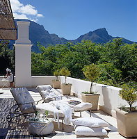 The wide terrace has a stunning view of the surrounding mountains and is furnished with comfortable sun-loungers and scatter cushions and lined with terracotta pots of ornamental kumquat trees