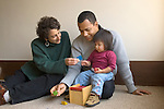 Berkeley CA Adoptive parents encouraging Guatemalan daughter, eighteen-months-old to do geometric shape block puzzle MR