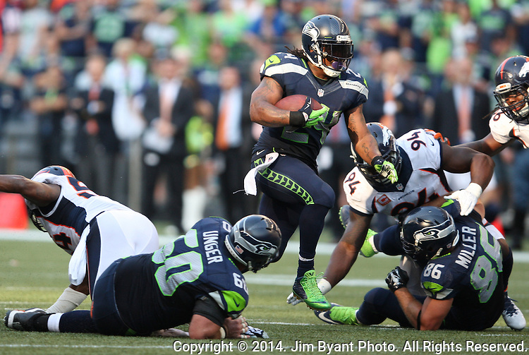 Seattle Seahawks running back Marshawn Lynch (24) looks for running room against  Denver Broncos in overtime at CenturyLink Field in Seattle, Washington on September 21, 2014.   Lynch ran for 88 yards and scored two touchdowns in the Seahawks 26-20 overtime win over the Broncos.  Providing blocking against the Broncos defenders is center, Max Unger (60) and tight end Zach Miller (86)  ©2014. Jim Bryant Photo. All rights Reserved.