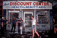 NYPD officers guard a looted store on Avenue A across from Tompkins Square park in the East Village on June 3, 1991. (© Frances M. Roberts)