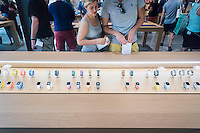Apple enthusiasts inspect a vitrine of Apple Watches in Williamsburg, Brooklyn in New York at the grand opening of Apple's first store in Brooklyn on Saturday, July 30, 2016. The tech company's new store features exposed brick, giant arch windows and at one story with a brick facade blends in with the neighborhood. Apple gave away commemorative tee-shirts to those attending the grand opening. (© Richard B. Levine)