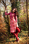 A pretty brunette in pink vintage clothing standing in a park , leaning onto a tree.