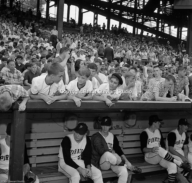 Pittsburgh PA: View of Pirate players and fans before the start of the HYPO Charity game between the Pittsburgh Pirates and Milwaukee Braves at Forbes Field.<br /> From left to right in the dugout, Tom Butters (31), Frank Bork (35) and Gene Freeze (12).<br /> The money raised by HYPO (Help Young Players Organize) was used to help local communities buy equipment and build ball fields.