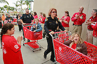 San Diego Police Officers wheel children into teh Target store on Sports Arena Boulevard in San Diego during the annual Shop-With-a-Cop on December 1, 2007.  Three hundred children participated in the event.  Some of them rose well before dawn in order to be ready for the fleet of buses that collected them from every corner of the county.  The buses took them to SeaWorld where they were paired up with an officer for the event.  After breakfast they made their way to the Target store in a huge, convoy of more than three hundred police vehicles with sirens blaring, lights flashing and Santa waving from a police helicopter hovering above them.  Each child had a $100 gift card to spend and many of them resisted the temptation to buy toys and choose instead to get clothes for themselves, their siblings or parents.