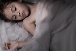 young child sleeping covered in light gauze wrap