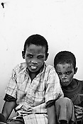 Young Somali refugees, Ali (10) and his sibling Abshir(7) wait outside the registration centre in IFO-1camp in the Dagahaley refugee camp in northeastern Kenya. Photo: Sanjit Das/Panos