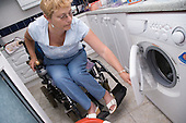 Woman wheelchair user loading the washing machine. MR