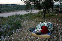 03.05.2003.Peace activists protest the building of the wall being built on Palestinian land. A protester sleeps next to the building site..