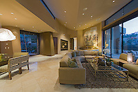Sectional couch is seen in ultra modern home with walls of glass at dusk