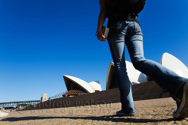A backpacker walks toward the Sydney Opera House  Sydney, New South Wales, AUSTRALIA.