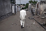 "KINSHASA, DEMOCRATIC REPUBLIC OF CONGO - FEBRUARY 12: Jika, a senior Sapeur takes a walk in his white diamond suit close to his home in the Mombele area on February 12, 2012 in Kinshasa, DRC. Jika loves Japanese fashion especially the designer Yohji Yamamoto. The word Sapeur comes from SAPE, a French acronym for Société des Ambianceurs et Persons Élégants or Society of Revellers and Elegant People and it also means, to dress with elegance and style"". Most of the young Sapeurs are unemployed, poor and live in harsh conditions in Kinshasa,  a city of about 10 million people. For many of them being a Sapeur means they can escape their daily struggles and dress like fashionable Europeans. Many hustle to build up their expensive collections. Most Sapeurs could never afford to visit Paris, and usually relatives send or bring clothes back to Kinshasa. (Photo by Per-Anders Pettersson)"