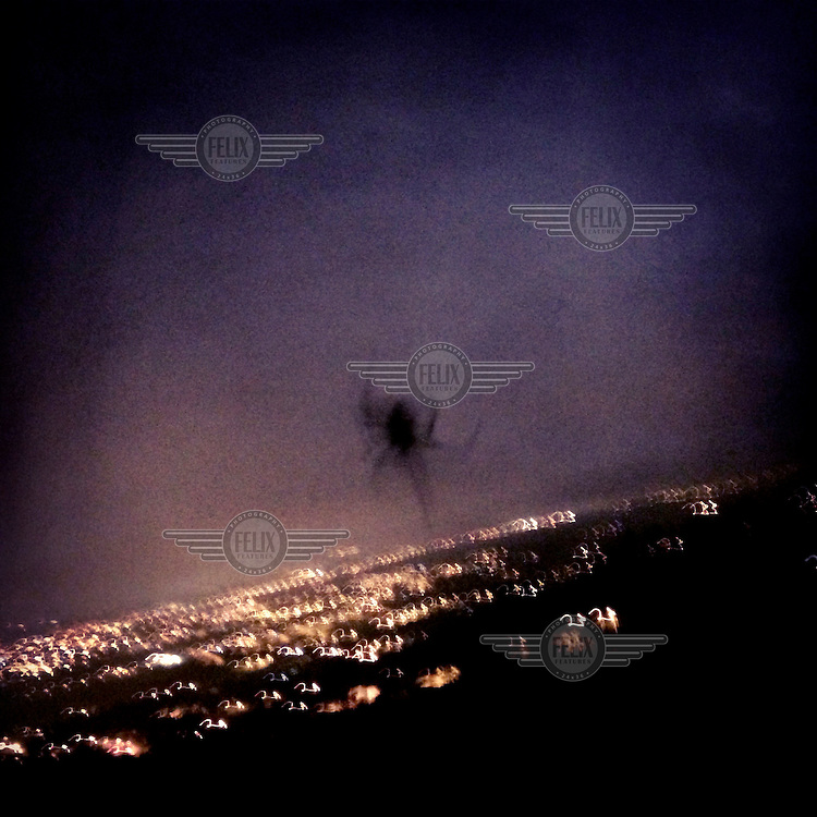 A spider appears to be crawling over the suburb of Tumbaco, seen through a window in Rumihuaico.