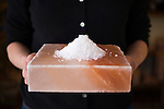Owner Jennifer Bitterman holds a Himalayan Salt plate topped with some New Zealand Marlborough Flakey salt at her store, The Meadow, a salt, chocolate, wine and flower shop in the North Mississippi neighborhood of Portland, OR