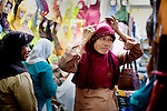 A woman tries on a veil at Pasar Aceh, or Aceh market, in Band Aceh, Indonesia, on Thursday, Nov. 19, 2009