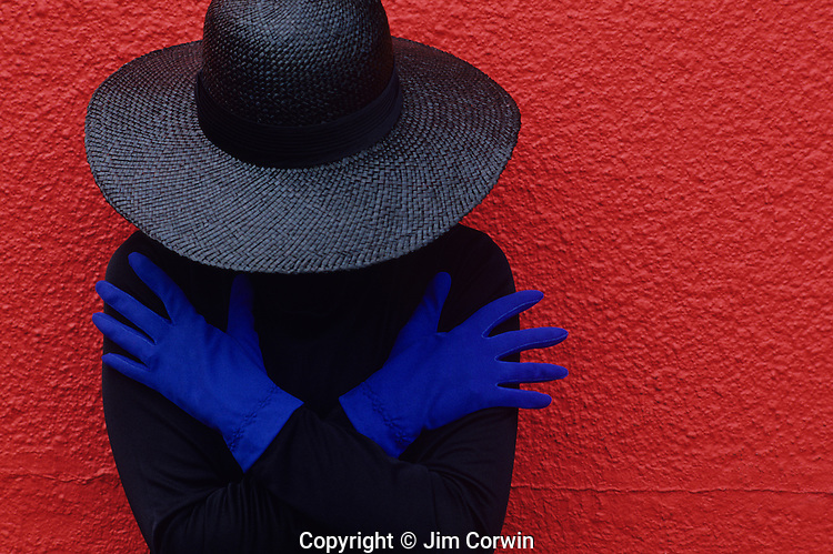 Woman in front of a red wall wearing blue gloves dressed in black clothes Seattle Washington State USA