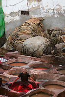 High angle view of dyeing pits, Chourara Tannery, Fez, Morocco, pictured on February 25, 2009 in the evening. Arms and legs working together to remove skins from the dyeing pit at the Chouara tannery which is the largest of the four ancient tanneries in the Medina of Fez where the traditional work of the tanners has remained unchanged since the 14th century. It is composed of numerous dried-earth pits where raw skins are treated, pounded, scraped and dyed. Tanners work in vats filled with various coloured liquid dyes derived from plant sources. Colours change every two weeks, poppy flower for red, mint for green, indigo for blue, chedar tree for brown and saffron for yellow. Fez, Morocco's second largest city, and one of the four imperial cities, was founded in 789 by Idris I on the banks of the River Fez. The oldest university in the world is here and the city is still the Moroccan cultural and spiritual centre. Fez has three sectors: the oldest part, the walled city of Fes-el-Bali, houses Morocco's largest medina and is a UNESCO World Heritage Site;  Fes-el-Jedid was founded in 1244 as a new capital by the Merenid dynasty, and contains the Mellah, or Jewish quarter; Ville Nouvelle was built by the French who took over most of Morocco in 1912 and transferred the capital to Rabat. Picture by Manuel Cohen.