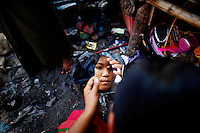 An illegal immigrant girl uses the mirror at her shelter at a rubbish dump site near Mae Sot December 22, 2009. Despite terrible living conditions and the fear of being sent back to their country, several hundred illegal immigrants from Myanmar live and earn an average of $1 per day collecting plastic at the rubbish dump near the border town of Mae Sot. Myanmar's long-standing political crisis has forced millions of people to cross the border for a better and safer life. The first refugees arrived and set up camps in the Myanmar-Thailand border in 1984. Now, there are over 140,000 refugees in nine official camps along Thailand's western border. Many more are expected to be in unofficial settlements.   REUTERS/Damir Sagolj (THAILAND)