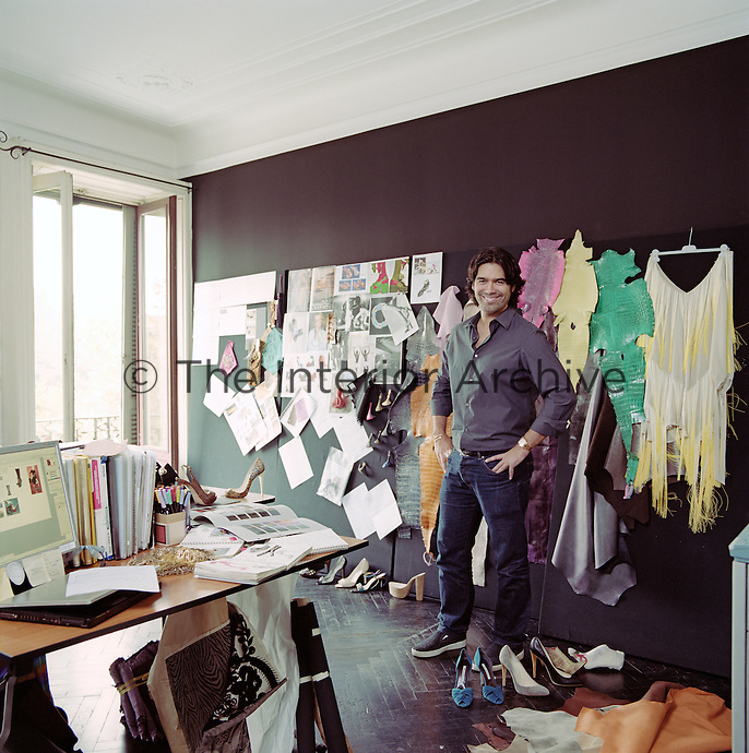 Brian Atwood surrounded by a creative clutter of swatches, sketches and photographs in his Milan studio