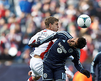 New England Revolution midfielder Scott Caldwell (6) and Sporting Kansas City midfielder Benny Feilhaber (10) battle for head ball.  In a Major League Soccer (MLS) match, Sporting Kansas City (blue) tied the New England Revolution (white), 0-0, at Gillette Stadium on March 23, 2013.