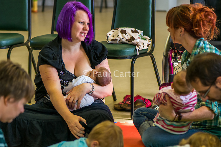 Breastfeeding a newly arrived baby at a singing and signing group whilst talking to the other mothers.