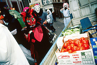 "Switzerland. Basel. Fasnacht Carnival. ""Clique""  is a group of persons playing music in the streets during the three days of the Carnaval. The group passes-by a van delivering vegetables (tomatoes of Spain, salads,..) to a shop. © 1997 Didier Ruef"