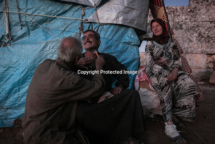 """In this Thursday, Sep. 26, 2013 photo, Syrian displaced men shave as a woman watchs in the sunset at the Kafr Ruma, an ancient roman ruins used as temporary shelter by those families who have fled from the heavy fighting and shelling in the Idlib province countryside of Syria. Dozens of families settled in the ancient ruins known as """"The Forgotten City"""" and declared human heritage by UNESCO, when the clashes between opposition fighters and government forces broke out in the region since more than two years ago. (AP Photo)"""
