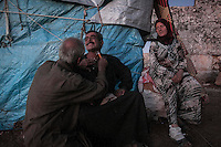 "In this Thursday, Sep. 26, 2013 photo, Syrian displaced men shave as a woman watchs in the sunset at the Kafr Ruma, an ancient roman ruins used as temporary shelter by those families who have fled from the heavy fighting and shelling in the Idlib province countryside of Syria. Dozens of families settled in the ancient ruins known as ""The Forgotten City"" and declared human heritage by UNESCO, when the clashes between opposition fighters and government forces broke out in the region since more than two years ago. (AP Photo)"
