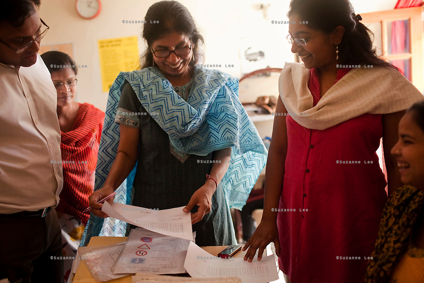 Meenu Vadera (center, in blue) checks test papers as she jokes with students and staff on 30th March 2010 in Azad Foundation.<br /> Currently training their 4th batch of students, Azad Foundation was set up by Meenu Vadera (Executive Director) in New Delhi, India, to train Indian women in driving services. Upon completion, these women work as personal drivers for a period of time before they upgrade their driving licences to commercial licences, allowing them to drive taxis. With this program, Azad aims to empower Indian women including those previously abused or trafficked, while making Delhi a safer place for women travelling in public transport. Photo by Suzanne Lee for Panos London