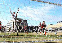 WASHINGTON, DC - NOVEMBER 25, 2012: Cole Seiler (14) of Georgetown University leaps high above Alex Bono (25) of Syracuse University but fails to get the ball during an NCAA championship third round match at North Kehoe field, in Georgetown, Washington DC on November 25. Georgetown won 2-1 after overtime and penalty kicks.