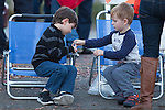 Two boys share a set of bells while waiting in chairs for the parade to start.