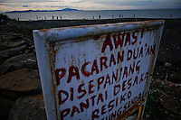 """Boys play football behind a warning sign placed by villagers at the beach in Banda Aceh December 12, 2012. The sign reads """"Be aware! Couples dating alone on this beach in our village doing it on their own responsibility"""". Some residents near the beach, together with many others including some local ulama, believe devastating 2004 tsunami that killed 170.000 people in Aceh province was the punishment from the God for those who broke Islamic laws and fear it might happen again. Indonesia is the world's most populous Muslim nation, but nowhere is the faith more strictly interpreted than in Aceh, sometimes referred to as the """"verandah of Mecca"""" because it was one of the first parts of the archipelago to turn to Islam. Aceh is Indonesia's only province to have implemented Sharia or Islamic laws.    REUTERS/Damir Sagolj (INDONESIA)"""