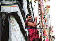 A monk from the Tantric college is  attaching one of the butter sculptures to a mast; the 3rd day of  Monlam Chenmo (the Great Prayer), in the monastery of Labrang. The sculptures made of yak butter and barley flour are only displayed at the end of the day to avoid the light of the sun, and pilgrims will come to see them and to pray deities until late in the night. Xiahe, China, 03/04/2007.