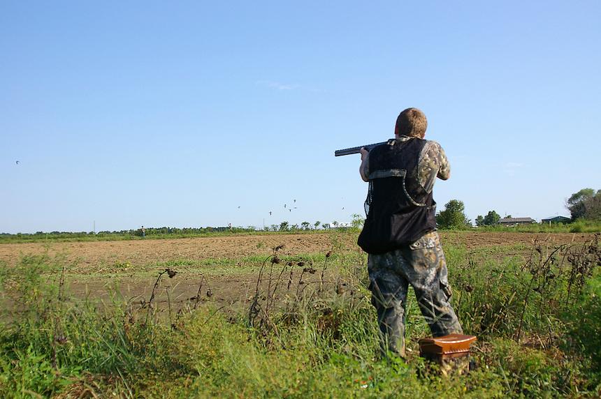 Mourning dove hunter aiming at flying doves, Cross County, Arkansas
