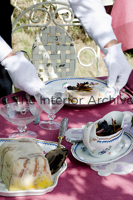 Detail of a starter being laid on the table at a grand al fresco lunch