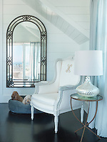 A contemporary iron-framed mirror reflects the light around this airy white-painted bedroom