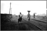 Daily wage labourers returning home from work. Contract worker are paid by the day and many are employed to load coal into trucks for private companies..India is the third largest producer of coal in the world and accounts for over 60% of India's energy requirements. It is estimated that the coal reserves are likely to last over a 100 years..03/2003