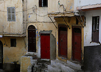 Medina Tangier, Morocco pictured on December 18, 2009. An atmospheric view of walls, doors and windows at haphazard angles in a corner of the old town. Tangier, the 'White City', gateway to North Africa, a port on the Straits of Gibraltar where the Meditaerranean meets the Atlantic is an ancient city where many cultures, Phoenicians, Berbers, Portuguese and Spaniards have all left their mark. With its medina, palace and position overlooking two seas the city is now being developed as a tourist attraction and modern port. Picture by Manuel Cohen