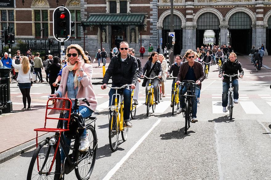 Nederland, Amsterdam, 30 mei 2015<br /> Fietsverkeer in de stad. Grote groep toeristen op gele huurfietsen. <br /> Foto: Michiel Wijnbergh