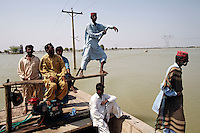 People are ferried across flood water, near Ghauspur, in Sindh Province, Pakistan.