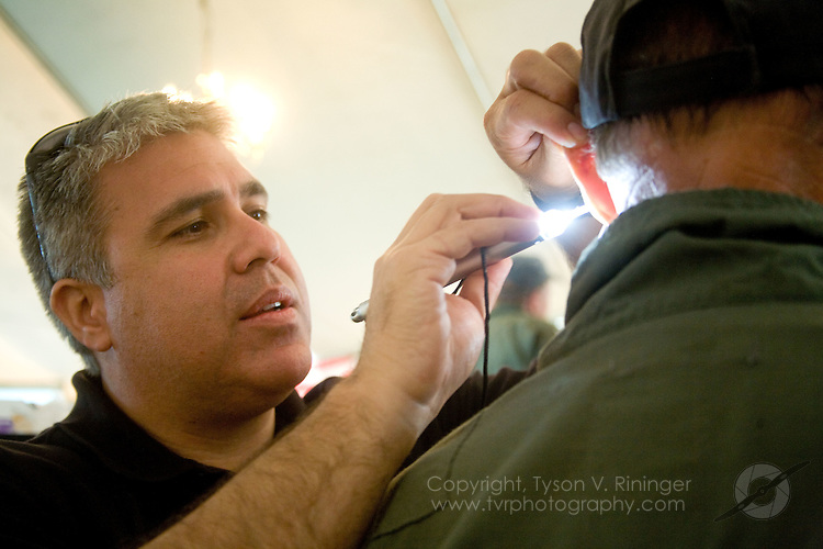 Robert Munoz of Westone Laboratories fits an Attenuating Custom Communications Earpiece System (ACCES) to participating All Red Star pilots.