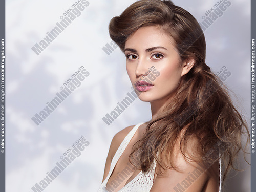 Artistic beauty portrait of a young woman with long light brown hair isolated on white wall background in a shadow of a tree