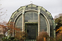 Facade of the Tropical Rainforest Glasshouse (formerly Le Jardin d'Hiver or Winter Gardens), 1936, Rene Berger, Jardin des Plantes, Museum National d'Histoire Naturelle, Paris, France. General view of the main Art Deco style entrance consisting of pillars in luminescent glass paste by Auguste Labouret, and wrought iron decoration by raymond Subes seen in the morning light. The lower railings, just visible in the foreground, were also made by Raymond Subes.