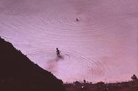 ISLANDA: paesaggio naturale. Persone che fanno il bagno nell'acqua calda contenuta in un cratere vulcanico generando delle onde concentriche.