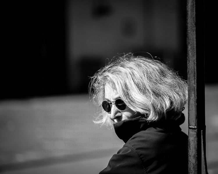 Woman in bright sunlight, wearing sunglasses, leaning against a pole.