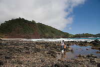 A father points something out to his son at a tide pool at Koki Beach, just past Hana town, Maui.