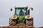 John Deere tractor harrowing a ploughed field against skyline
