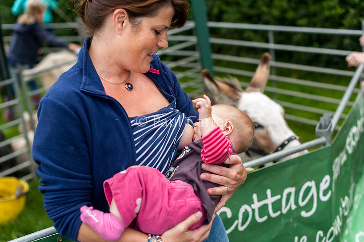 A mother breastfeeds her baby at a pre-school open day event - a travelling farm.<br /> <br /> 30 August 2012<br /> Hampshire, England, UK