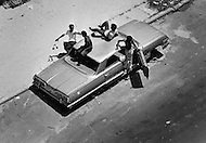 August 1971, Brooklyn, New York City, New York State, USA --- The long, hot summer of August 1971 exacerbated tensions in the black ghetto of Bronx. Poor housing, poverty, unemployment and crime did not facilitate the poor inhabitants during the heatwave. Teenagers play with a stolen, abandoned car in a street. --- Image by © JP Laffont/Sygma/Corbis
